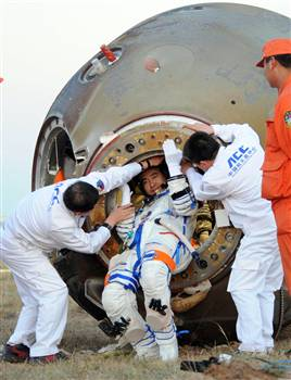 A taikonaut emerges from China\'s Shenzhou 7 spacecraft after a successful orbital flight