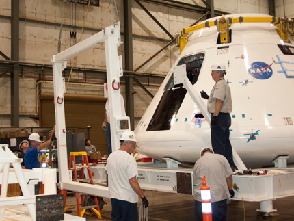 "Technicians at NASA Dryden install the ""goalpost"" fixture to the Orion crew module integration stand during conversion of the stand into a transportation fixture for airlift of the module to the White Sands Missile Range in New Mexico. The crew module will be used in the first Orion Launch Abort System pad abort flight test, expected in early 2010. (NASA Photo / Jim Ross)"