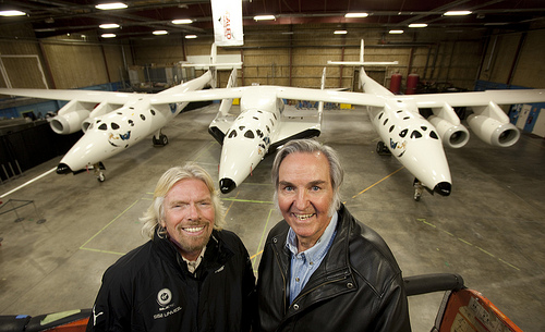 Sir Richard Branson (L) and Burt Rutan pose for a photo in front of the SpaceShip2 resting under the Mothership WhiteKnight2 inside a hangar in Mojave,Ca.
