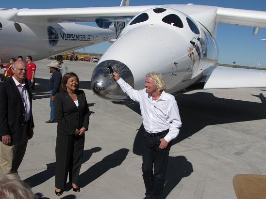 New Mexico Gov. Susana Martinez and Richard Branson pose in front of SpaceShipTwo and WhiteKnightTwo. (Credit: Douglas Messier)