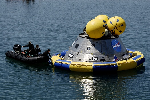 Members of the U.S. Air Force 920th Rescue Wing secure a flotation collar around the mockup Orion crew module at the Trident Basin at Port Canaveral, Fla. during testing in 2009. The post-landing Orion Recovery Test helped determine what kind of motion astronauts will experience after landing, as well as what recovery teams should expect. (Credit: NASA/Kim Shiflett)