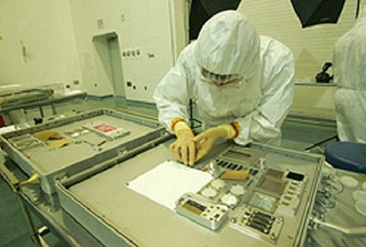 "Miria Finckenor, materials engineer at the Marshall Space Flight Center, removes a sample from a Materials International Space Station Experiment (MISSE) Passive Experiment Container at Langley Research Center. Approximately 35 members of the MISSE team traveled from across the country to witness the ""grand opening"" of MISSE-1 and 2 in 2005. (Credit: NASA/Jeff Caplan)"