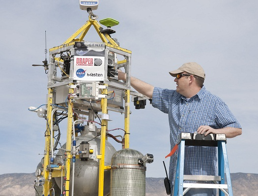 Tye Brady, principal investigator for Draper Lab's GENIE flight control system, makes final adjustments to the system on Masten Space Systems' Xombie technology demonstration rocket before liftoff. (Credit: NASA/Tom Tschida)