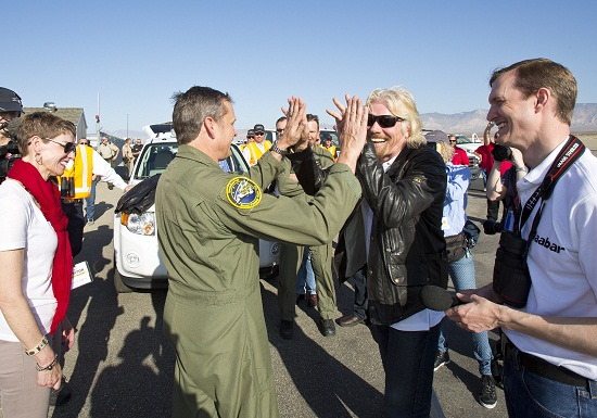 "Sir Richard Branson ""high tens"" with SpaceShip2 test pilot Mark Stuckey following the successful first powered flight of SpaceShipTwo. At left is Mark Stuckey's wife Cheryl and at right is Virgin Galactic President and CEO George Whitesides..  The spacecraft was dropped rom its ""mothership"", WhiteKnight2 over the Mojave, CA area, April 29, 2013 at high altitude before firing its hybrid power motor. (Credit: Virgin Galactic)"