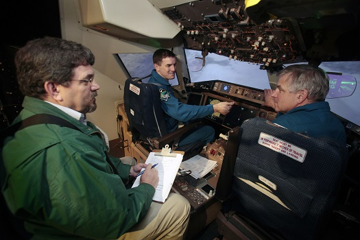 Bruce Jackson, an aerospace engineer at NASA's Langley Flight Research Center, briefs astronauts Rex Walheim, left, and Gregory Johnson as they evaluate Sierra Nevada Corporation's Dream Chaser landing simulation in the Cockpit Motion Facility. (Credit: NASA/David C. Bowman)