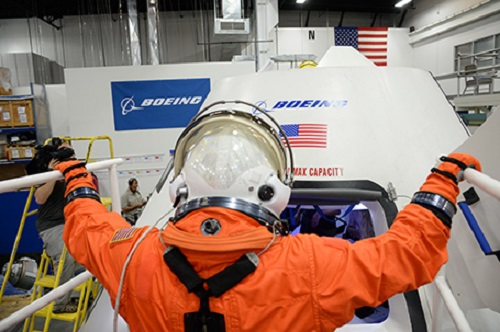 NASA astronaut climbs aboard a mock-up CST-100 spacecraft July 22 at The Boeing Company's Houston Product Support Center. (Credit: NASA)