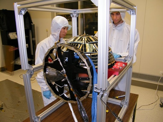 Former CU-Boulder students Mark Sakaguchi and Bruce Davis test the DANDE satellite. (Credit: CU-Denver)
