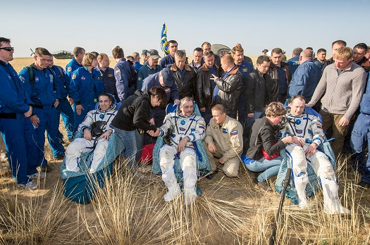 Expedition 36 Flight Engineer Chris Cassidy of NASA, left, Commander Pavel Vinogradov of the Russian Federal Space Agency (Roscosmos), center, and, Flight Engineer Alexander Misurkin of Roscosmos, sit outside the Soyuz capsule just minutes after they landed. (Credit: NASA/Bill Ingalls)