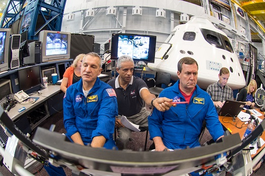 Astronauts Rick Linnehan and Mike Foreman work with simulation instructor Juan Garriga (center) to prepare for their first ascent simulation inside a mockup of NASA's new Orion spacecraft at Johnson Space Center. (Credit:  NASA)