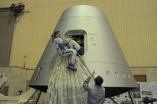 A cosmonaut practices emergency egress from a mockup of Russia's advanced crew transport. (Credit: Energia)