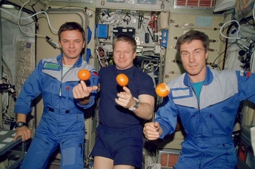 The Expedition One crew members are about to eat fresh fruit onboard the Zvezda Service Module of the Earth-orbiting International Space Station. (Credit: NASA)