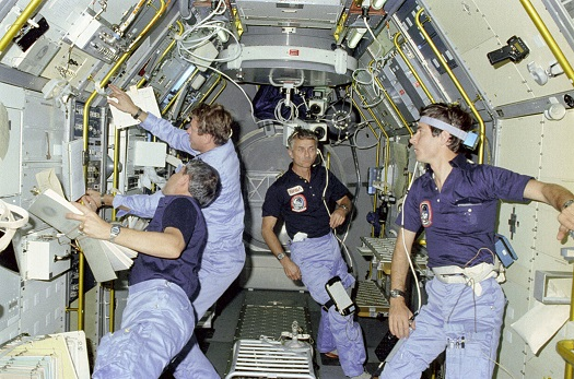 Aboard Spacelab-1 during STS-9 in 1983 are, from left, Mission Specialist Robert Parker, Payload Specialist Byron Lichtenberg, Mission Specialist Owen Garriott and Payload Specialist Ulf Merbold. (Credit: NASA)