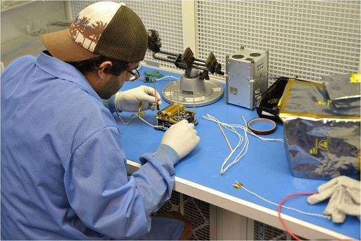 An engineer works on the FIREBIRD CubeSat. (Courtesy of NASA)