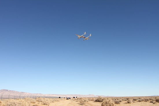 WhiteKnightTwo flies over a group of spectators watching SpaceShipTwo land. (Credit: Douglas Messier)