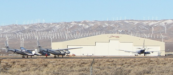 Pre-flight checks are made on WhiteKnightTwo and SpaceShipTwo. In the background are a 747-422 dwarfed by the Stratolaunch hanger. (Credit: Douglas Messier)