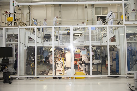 Engineers work on Orion's crew module inside a temporary clean room set up inside the Operations and Checkout facility at Kennedy Space Center. Welding on the crew module was completed this month. (Credit: NASA)