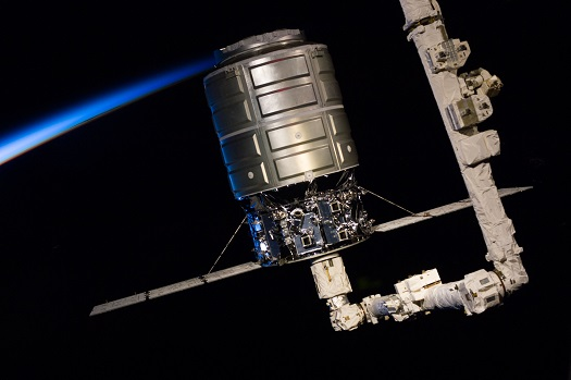This medium close-up view, photographed by one of the Expedition 37 crew members, shows the first Cygnus commercial cargo spacecraft built by Orbital Sciences Corp. attached to the end of the robotic arm (Canadarm2) on the International Space Station. (Credit: NASA)