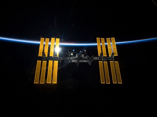 The International Space Station, backdropped by the blackness of space and the thin line of Earth's atmosphere. (Credit: NASA)