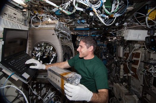 Aboard the International Space Station, astronaut Mike Hopkins works with a cell array for the Selectable Optics Diagnostic Instrument-Diffusion Coefficient in Mixtures 2 (SODI-DCMIX 2) investigation. Findings may help refine petroleum reservoir models for more efficient extraction of oil resources. (Credit: NASA)