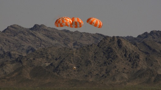 A test version of NASA's Orion spacecraft descends under its three main parachutes above the U.S. Army Proving Ground in Arizona in the agency's most difficult test of the parachutes system's performance. (Credit: NASA/Rad Sinyak)