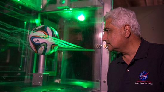 Dr. Rabi Mehta uses smoke and lasers to inspect the flow pattern around an Adidas Brazuca football. (Credit: NASA)