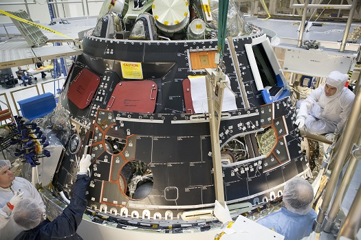 Inside the Operations and Checkout Building high bay at NASA's Kennedy Space Center in Florida, technicians dressed in clean-room suits install a back shell tile panel onto the Orion crew module. (Credit:  NASA/Dimitri Gerondidakis)