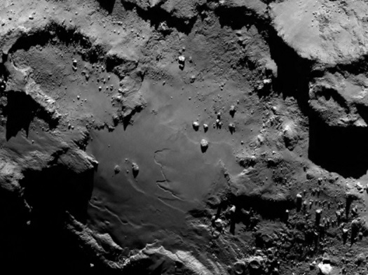 Stunning close up detail focusing on a smooth region on the 'base' of the 'body' section of comet 67P/Churyumov-Gerasimenko. The image was taken by Rosetta's OSIRIS narrow-angle camera and downloaded today, 6 August. The image clearly shows a range of features, including boulders, craters and steep cliffs. The image was taken from a distance of 130 km and the image resolution is 2.4 metres per pixel.  Credits: ESA/Rosetta/MPS for OSIRIS Team MPS/UPD/LAM/IAA/SSO/INTA/UPM/DASP/IDA