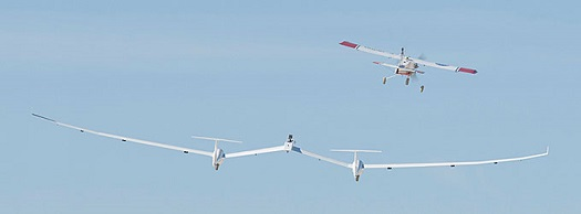 One of NASA Armstrong's DROID small unmanned research aircraft tows the twin-fuselage towed glider into the blue sky on its first test flight. (Credit: Tom Tschida/NASA Armstrong)