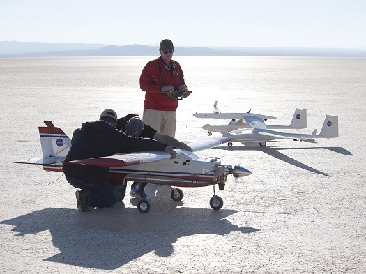 Small unmanned aircraft technician Derek Abramson and glider pilot Red Jensen, hold back the DROID tow plane while pilot Gerald Budd runs through some last minute checks. (Credit: Tom Tschida/NASA Armstrong)