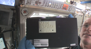 "ISS Commander Barry ""Butch"" Wilmore holds up the first 3-D printed part made in space. (Credit: Made in Space)"
