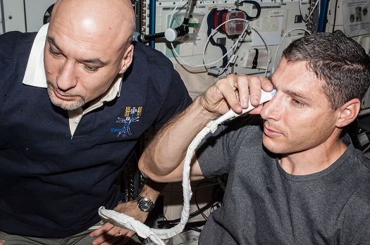 NASA astronaut Michael Hopkins and European Space Agency astronaut Luca Parmitano perform ultrasound eye imaging as part of the Fluid Shifts investigation during Expedition 37 on the International Space Station. (Credit: NASA)
