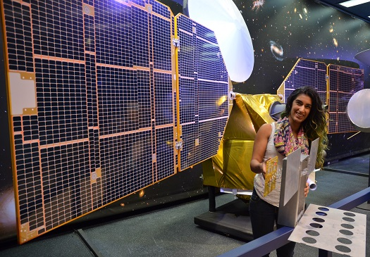 The full-scale mock-up of NASA's MarCO CubeSat held by Farah Alibay, a systems engineer for the technology demonstration, is dwarfed by the one-half-scale model of NASA's Mars Reconnaissance Orbiter behind her. (Credit: NASA/JPL-Caltech)