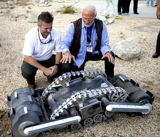 Rob Mueller, NASA senior technologist in the Surface Systems Office at the Kennedy Space Center, left, talks with former NASA Gemini and Apollo astronaut Buzz Aldrin during a demonstration of the Regolith Advanced Surface Systems Operations Robot, or RASSOR. The robot has been tested at Kennedy's Swamp Works. A similar spacecraft could be used to collect samples or excavate a landing pad for future landers.(Credit: NASA/Ben Smegelsky)