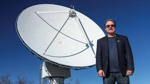 Morehead State University Professor Benjamin Malphrus, who is leading the Lunar IceCube mission, stands in front of the university's 21-meter ground station antenna that will be handling the mission's communications needs. (Credit: NASA)
