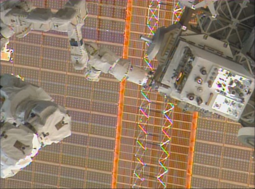 RRM operations demonstrate satellite-servicing technologies using the RRM module (right) and the Dextre robot (top center). Behind them, the ISS solar array is visible. (Credit: NASA)