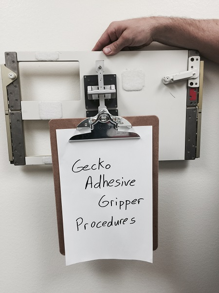 The gecko grippers could one day be used to mount objects on the inside of the International Space Station. This image shows a gripper attaching a clipboard to a spare panel -- the same kind found inside the United States' modules of the station. (Credits: NASA/JPL-Caltech)