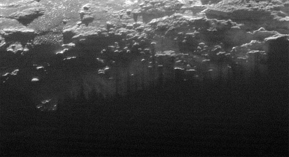 Near-Surface Haze or Fog on Pluto: In this small section of the larger crescent image of Pluto, taken by NASA's New Horizons just 15 minutes after the spacecraft's closest approach on July 14, 2015, the setting sun illuminates a fog or near-surface haze, which is cut by the parallel shadows of many local hills and small mountains. The image was taken from a distance of 11,000 miles (18,000 kilometers), and the width of the image is 115 miles (185 kilometers). (Credits: NASA/JHUAPL/SwRI)