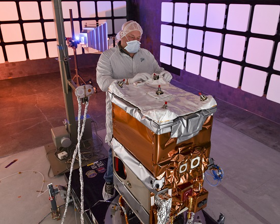 A Ball Aerospace engineer adjusts the thermal insulation on NASA's Green Propellant Infusion Mission spacecraft bus following integration of the propulsion system. (Credit: Ball Aerospace)