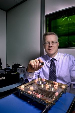 NASA laser expert Mike Krainak and his team plan to replace portions of this fiber-optic receiver with an integrated-photonic circuit, whose size will be similar to the chip he is holding. The team then plans to test the advanced modem on the International Space Station. (Credits: NASA/W. Hrybyk)