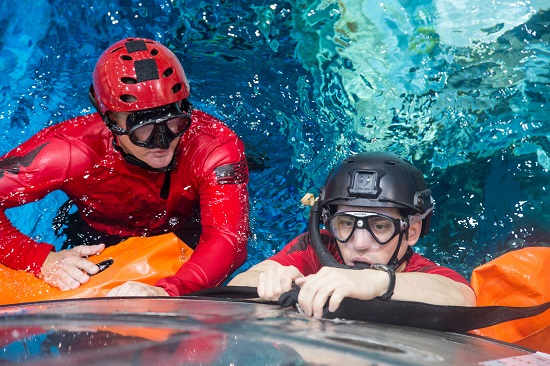 Master Sgt. Chris Seinkner, 308th Rescue Squadron, Patrick AFB, Fla., teams up with Staff Sgt. Eli Reynolds, of the 88th Test and Evaluation Squadron, Nellis AFB, Nev., to install the stabilization collar on the Orion Capsule during a recent exercise at NASA's Neutral Buoyancy Lab in Houston, Texas. (Credit; NASA)