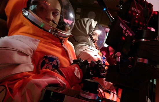 PoSSUM students learn to operate space-qualified instrumentation in spacesuits. (Credit: Project PoSSUM)