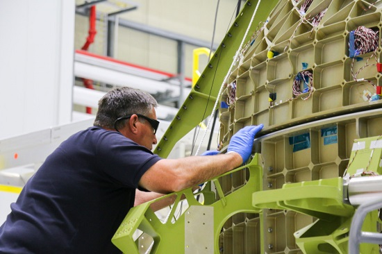 A Boeing engineer works on joining the upper and lower half of a Starliner structural test article. (Credit: Boeing)