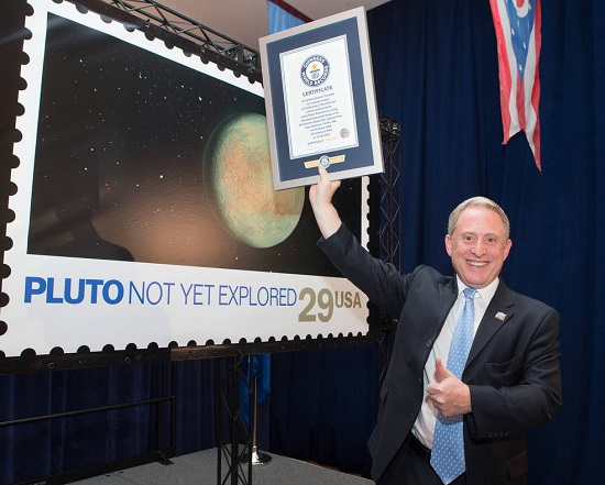New Horizons Principal Investigator Alan Stern celebrates a Guinness World Record certificate on July 19 at U.S. Postal Service Headquarters in Washington, D.C. (Credit: Dan Afzal, U.S. Postal Service)