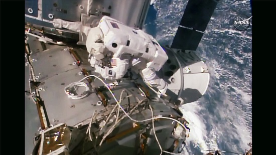 Spacewalker Kate Rubins works outside the International Space Station with the SpaceX Dragon space freighter just below her. (Credit: NASA TV)