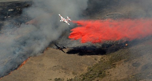 An aircraft drops chemicals on wildfire at Vandenberg Air Force Base. (Credit: USAF)