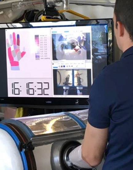 Test subject performing glove box operations in front of data collections screen wherein real time glove pressures and several views of glove box can be viewed during testing. (Credit: NASA)