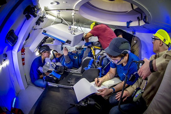 Astronaut Eric Boe evaluates Boeing Starliner spacesuit in mockup of spacecraft cockpit. (Credit: Boeing)